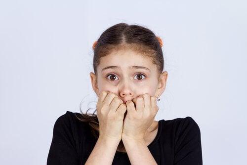 Meisje houdt angstig haar handen voor haar mond