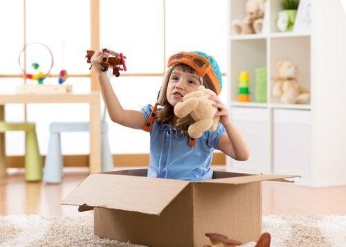 Kind speelt met speelgoed en kartonnen doos