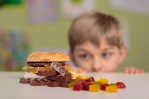 Jongen kijkt naar hamburger en snoep