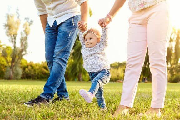 Ouders met een baby die leert lopen