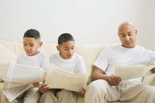 Vader leest de krant en zoons imiteren gedrag