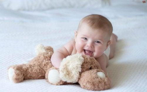 Een baby met een van zijn doopcadeau's