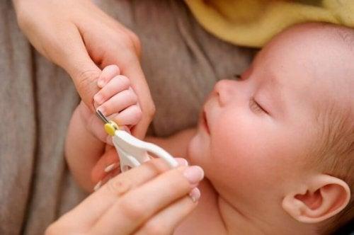 Moeder knipt de nagels van een slapende baby
