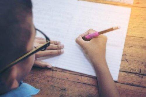 Jongen schrijft in een schrift
