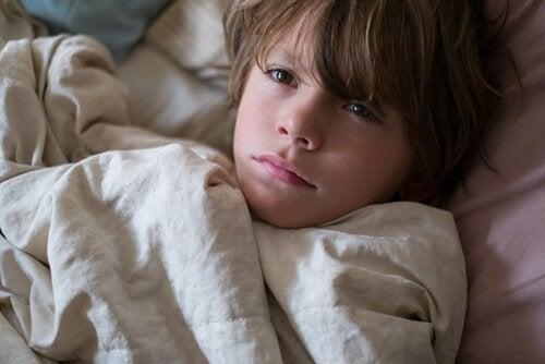 Jongen ligt bang in bed