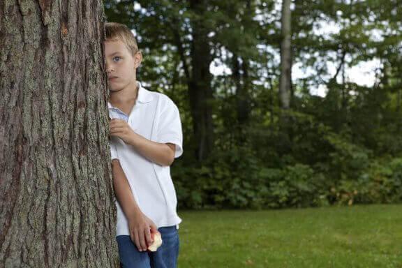 Jongen verstopt zich achter een boom