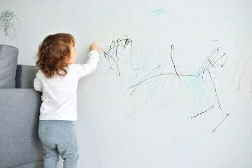 Kind maakt tekening op de muur