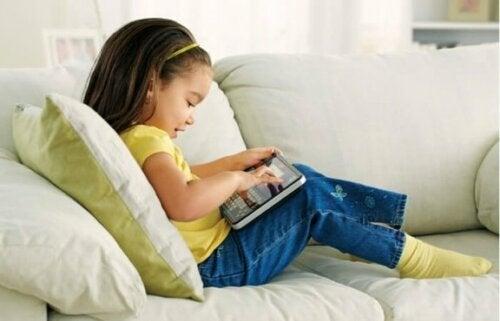 Meisje zittend op bank met tablet