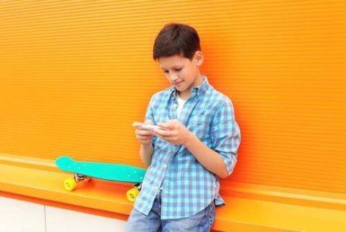 Jongen speelt iets op zijn mobiel