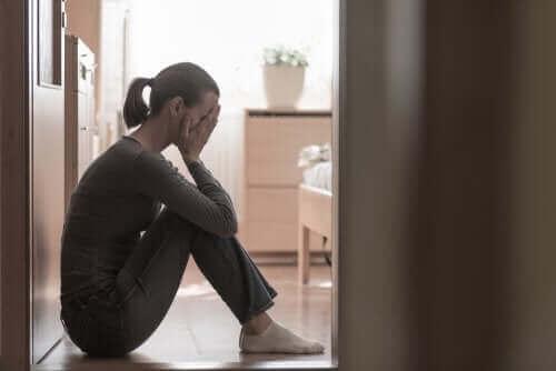 Een huilende moeder zittend op de vloer