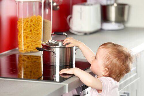 Een kind raakt een hete pan aan