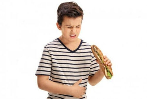 Jongen met indigestie eet broodje