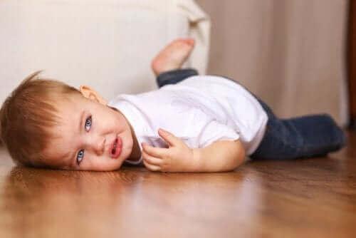 Kind ligt met driftbui op de grond