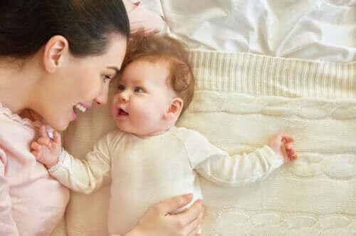 Moeder en baby liggen op bed
