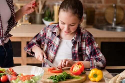 Kind helpt met koken door de groenten te snijden