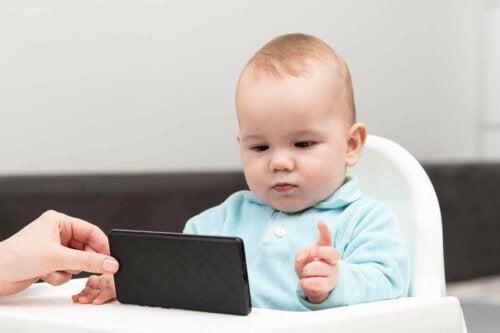 Baby kijkt op mobiel